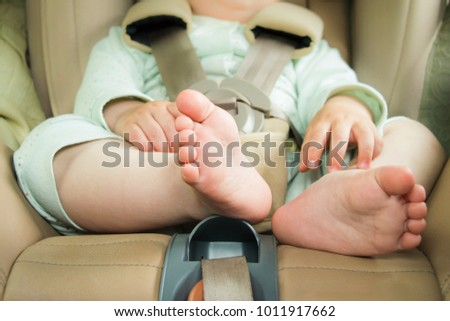 Small baby sitting in special car seat with safety seabelts, Safety in car concept, protection of child in travel, children feet in baby seat Royalty-Free Stock Photo #1011917662