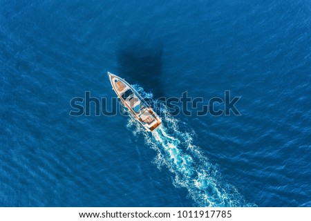Yacht at the sea in Europe. Aerial view of luxury floating ship at sunset. Colorful landscape with boat in marina bay, blue sea. Top view from drone of yacht. Luxury cruise. Seascape with motorboat Royalty-Free Stock Photo #1011917785