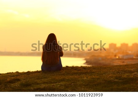 Back view backlight portrait of a single woman watching a sunset on the city with a warm light in the background #1011923959