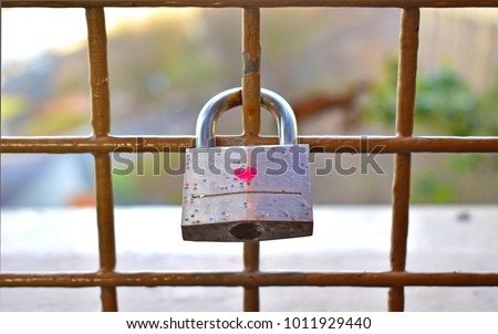 Padlock with one heart shape painting in the middle hanging on the middle of the brown metal fence background blurred colourful bokeh, feeling love forever. Concept Valentine's day or Wedding symbol.