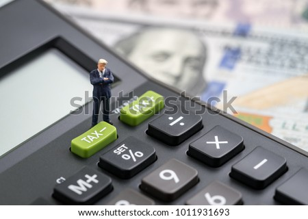 Tax cuts or reduce concept, miniature people business man president standing with TAX minus button on calculator with background of blurred US Dollar banknotes, United States government tax overhaul. #1011931693