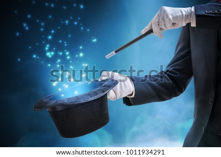 Magician or illusionist is showing magic trick. Blue stage light in background. Royalty-Free Stock Photo #1011934291