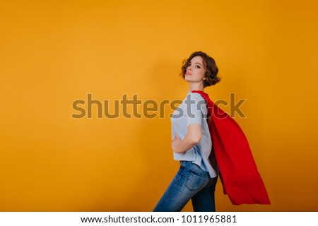 Lovely lady with curly hairstyle ready for new year carnival. Portrait of attractive superwoman in red mantle isolated on yellow background. #1011965881
