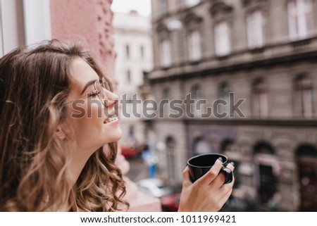 Inspired girl in trendy glasses posing with eyes closed on blur city background during tea time. Close-up photo of sensual dark-haired lady relaxing in morning with tasty coffee. #1011969421
