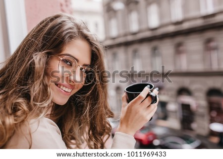 Close-up portrait of wonderful woman holding cup of latte on blur city background and looking to camera. Photo of ecstatic long-haired brunette girl wears glasses enjoying town views from window. #1011969433