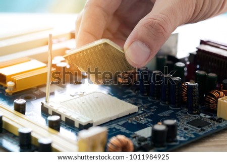 Hand of computer engineering brings computer cpu processor memory change components into socket processor for maintenance.Technology and development concept #1011984925