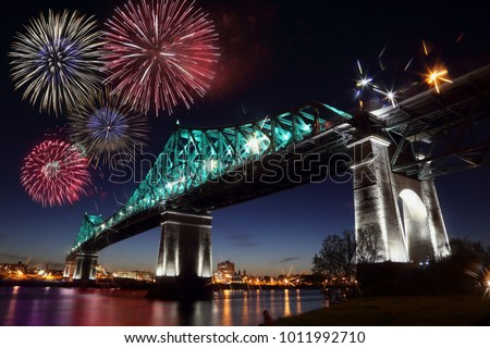 Colorful fireworks explode over bridge, reflection in water. Montreal's 375th anniversary. luminous colorful interactive Jacques Cartier Bridge. Bridge panoramic colorful silhouette by night.