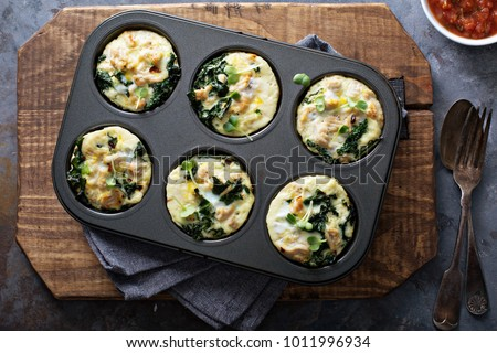 High protein egg muffins with kale and ground turkey in a muffin tin overhead shot Royalty-Free Stock Photo #1011996934