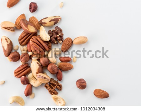 Background of nuts - pecan, macadamia, brazil nut, walnut, almonds, hazelnuts, pistachios, cashews, peanuts, pine nuts - with copy space. Isolated one edge. Top view or flat lay #1012034308