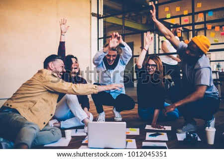 Cheerful male and female students celebrating winning in college contest giving high five, emotional multiracial members of crew excited with success in productive working process on startup Royalty-Free Stock Photo #1012045351
