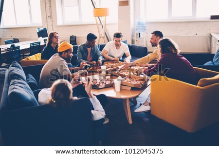 Young male and female coworkers having lunch break in office eating pizza and communicating, crew of young colleagues sitting in coworking space having pizza party together enjoying free time #1012045375