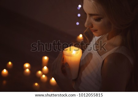Beautiful young woman holding candle in dark room #1012055815