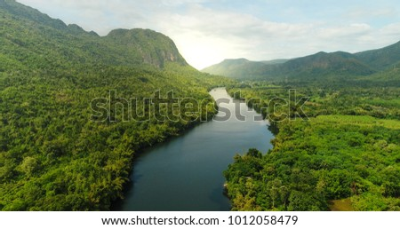 Beautiful natural scenery of river in southeast Asia tropical green forest  with mountains in background, aerial view drone shot #1012058479