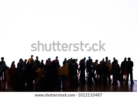 Silhouette of a large group of unrecognizable people. High contrast mob, squad, or crew of men and women. Big crowd or team on white with space for text. High contrast miniature photo. #1012110487