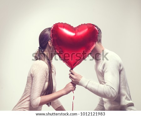 Valentine Couple. Beauty Girl and her Handsome Boyfriend holding heart shaped air balloon and kissing. Happy Joyful Family. Love. Happy Valentine's Day #1012121983
