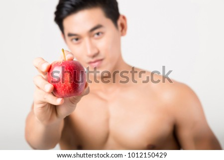Sportsman Bites Green Apple After Training. Fitness and healthy lifestyle concept. Studio shot on white background. #1012150429
