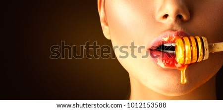 Honey dripping from honey dipper on sexy girl lips. Thick honey dipping from the wooden honey spoon. Beauty model woman open mouth, model eating nectar. Healthy food concept, diet, dessert #1012153588