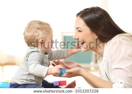 Side view portrait of a baby and mother playing together on the floor at home #1012207228