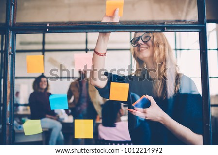 Smiling young female employee in stylish spectacles using stickers for creation strategy of working project during brainstorming session, skilled team member making notes presenting idea of startup #1012214992