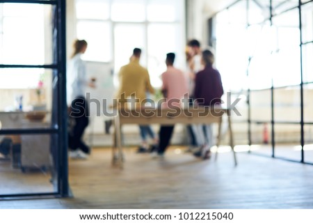 Blurred image, people silhouette collaborating in office interior. Defocused space for your information, teamwork process. Group of coworkers discussing ideas. Colleagues having informal work meeting Royalty-Free Stock Photo #1012215040