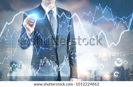 Businessman with a glowing marker drawing a graph. A cloudy day city background. HUD Toned image double exposure mock up #1012224862