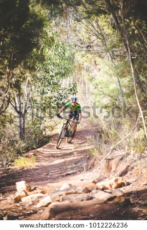 Wide angle view of a mountain biker speeding downhill on a mountain bike track in the woods #1012226236