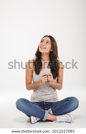 Full-length picture of young woman in jeans and sneakers sitting with legs crossed on the floor with silver smartphone in hand over white wall #1012227085