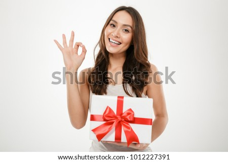 Picture of young woman holding present box with red bow and showing OK sign isolated over white background