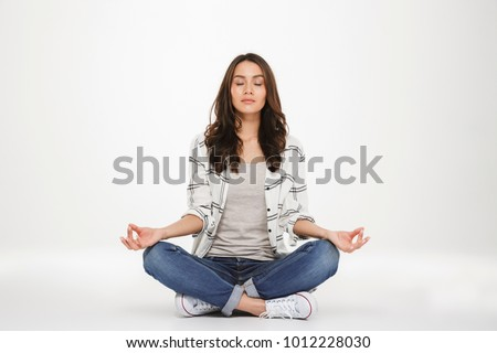Full-length picture of concentrated woman in casual clothes meditating with closed eyes while sitting in lotus pose on the floor isolated over white wall #1012228030