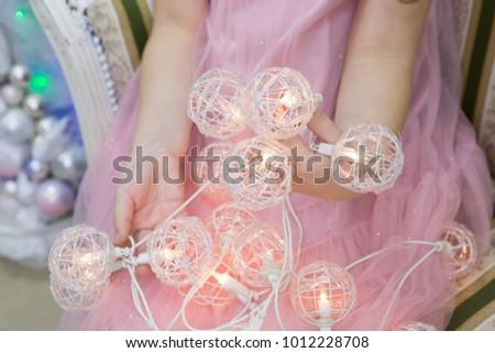 Children's hands holding tree garland  #1012228708