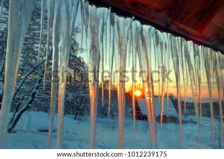 Winter sunrise scene with hanging icicles Royalty-Free Stock Photo #1012239175