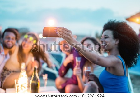 Happy friends taking selfie with smartphone at beach party outdoor - Young people having fun at kiosk bar drinking champagne - Soft focus on mobile cell phone - Youth lifestyle and vacation concept #1012261924