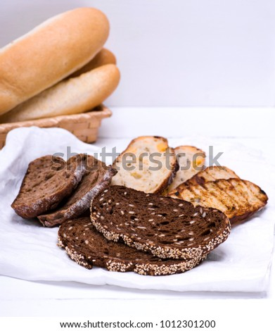 pieces of rye, white and with spices of bread on a white napkin #1012301200