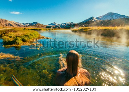 Beautiful female back packer traveler relaxing in the natural hot springs of LANDMANNALAUGAR, Iceland #1012329133