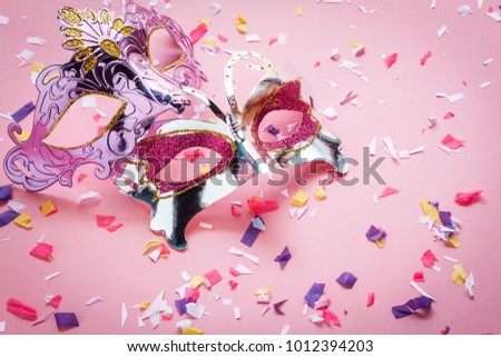 Table top view aerial image of beautiful couple carnival mask background.Flat lay essential accessory on modern rustic pink wallpaper at home office desk studio. Copy space for creative design text.