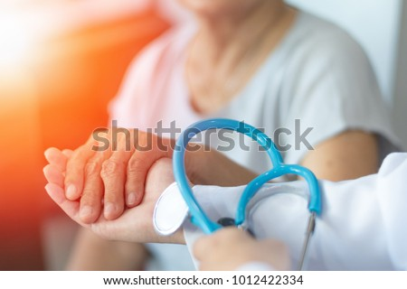 Geriatric doctor or geriatrician concept.  Doctor physician hand on happy elderly senior patient to comfort in hospital examination room or hospice nursing home or wellbeing county. Royalty-Free Stock Photo #1012422334