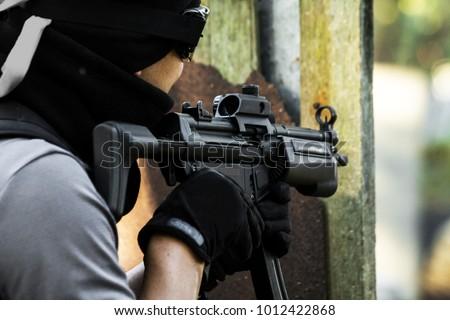 Shooter aiming assault rifle at target. #1012422868