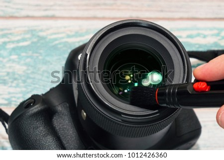 Taking care of proffesional photographic equipment concept. Cleaning the front lens of a digital SLR camera with brush tool, dust remove for making better shots. Close-up capture, selective focus.