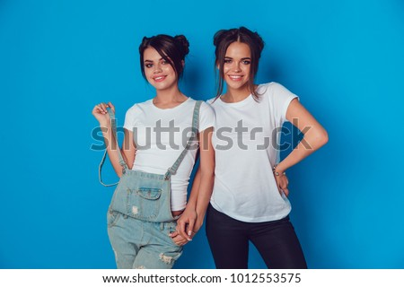 Attractive women in a white t-shirts stands on a blue background. Mock-up. #1012553575