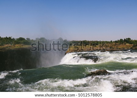 "The edge of Victoria Falls in Zimbabwe, near Livingstone Island and the naturally formed ""Devil's Pool"", where tourists can swim near the edge in the dry season #1012578805"