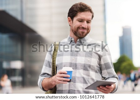 Smiling young man standing on a city street drinking a cup of coffee and using a digital tablet #1012641778