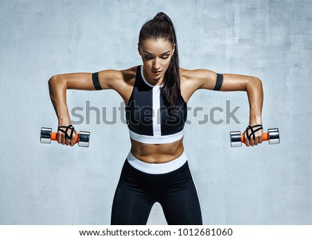 Athletic woman doing exercise for arms. Photo of muscular fitness model working out with dumbbells on grey background. Strength and motivation #1012681060