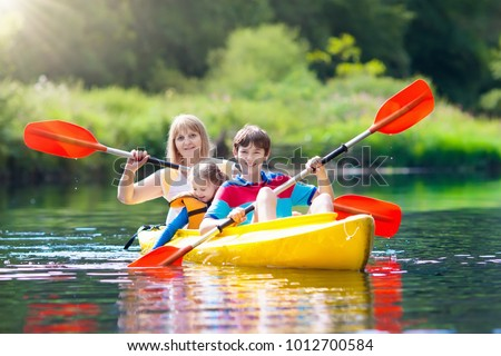 Child with paddle on kayak. Summer camp for kids. Kayaking and canoeing with family. Children on canoe. Little boy on kayak ride. Wild nature and water fun on summer vacation. Camping and fishing. #1012700584