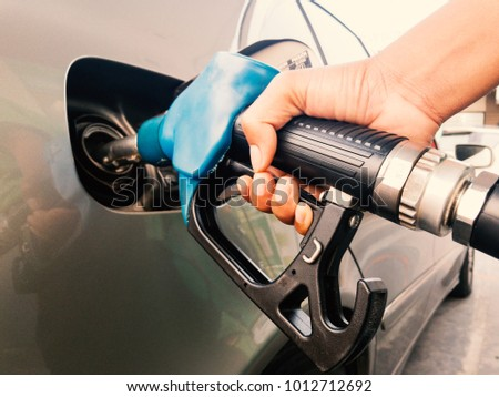 Hand holding gasoline nozzle for car refueling at gas station Royalty-Free Stock Photo #1012712692