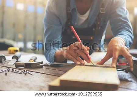 Carpenter working on woodworking machines in carpentry shop. A man works in a carpentry shop. #1012759555