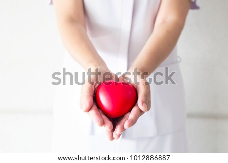 A beautiful nurse in white uniform holding a red heart in her hand. Delivered to patients in the hospital. #1012886887
