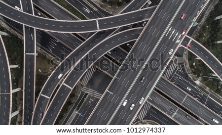 Aerial view of highway and overpass in city on a cloudy day #1012974337