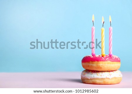 Donuts with candles on a pink and blue background, concept birthday. Copy space. #1012985602