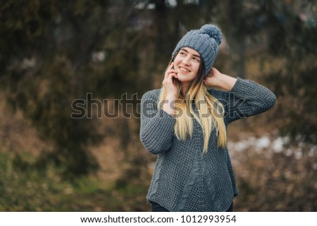 Happy girl in the knitted hat talking on the phone in the park. #1012993954