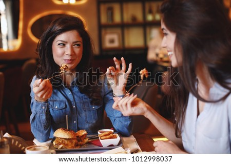 Two young women at a lunch in a restaurant Royalty-Free Stock Photo #1012998037